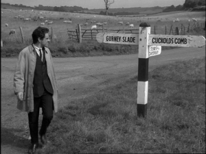 A black and white photo of a man standing at a crossroads, with a signpost -- one arrow says